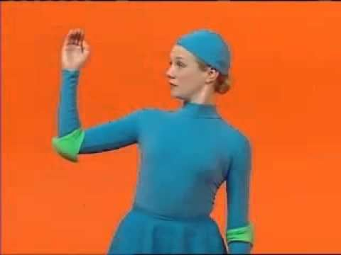 One of the casts of 4 Square, a Canadian television show for kids, wearing all blue outfits and raising her hand with an orange background.