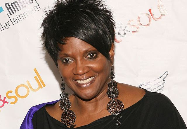 Anna Maria Horsford smiling while wearing a big necklace, earrings, and black blouse