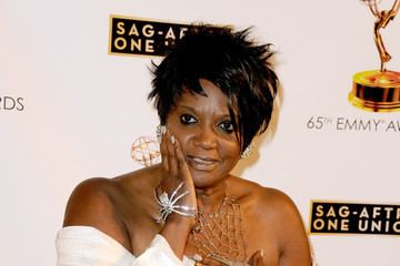 Anna Maria Horsford smiling while her hand on her face and wearing a white dress, necklace, and spider bracelet