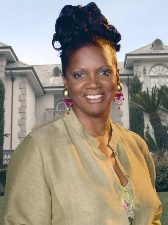Anna Maria Horsford smiling while wearing a beige blazer, floral inner top, and earrings