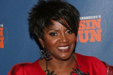 Anna Maria Horsford smiling while wearing a red dress, earrings and necklace