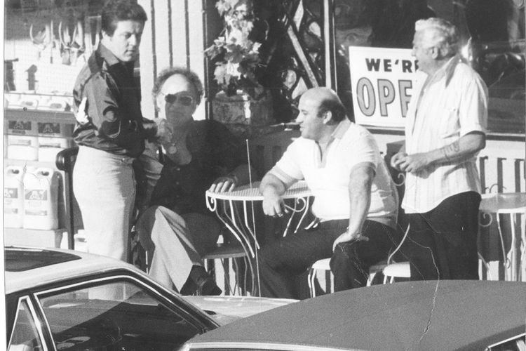 Anthony Spilotro wearing a black jacket and white pants together with his three friends outside the café.