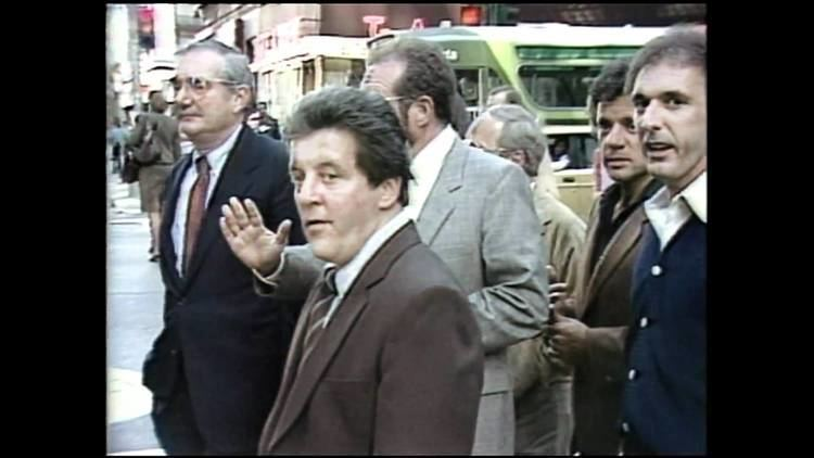 Anthony Spilotro wearing a suit and a striped tie surrounded by people.