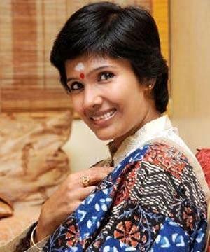 Anuradha Sriram smiling while wearing a blue and brown dress