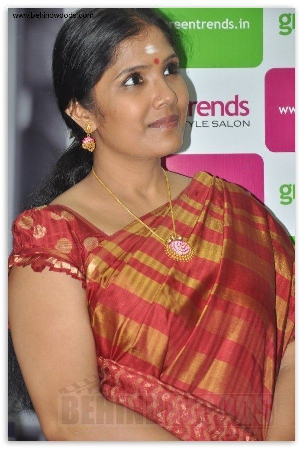 Anuradha Sriram smiling while looking afar and wearing a red and gold dress, earrings, and necklace