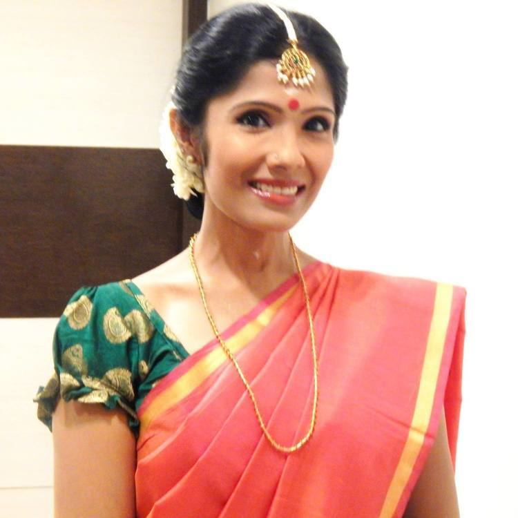 Anuradha Sriram smiling while wearing a green and orange dress, necklace, and headdress