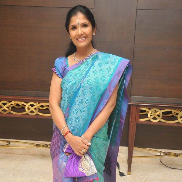 Anuradha Sriram smiling while wearing a blue and violet dress and some pieces of jewelry