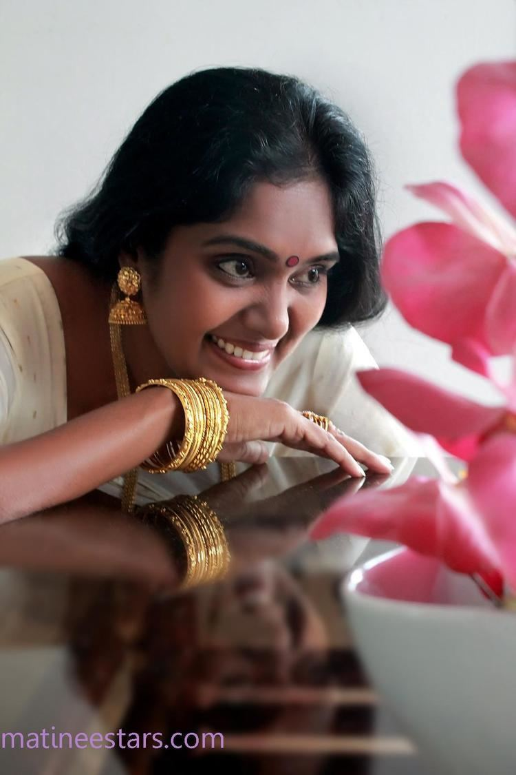 Archana (actress) with black hair, wearing gold earrings, necklace, rings, and bracelets with a pink flowers in front of her.