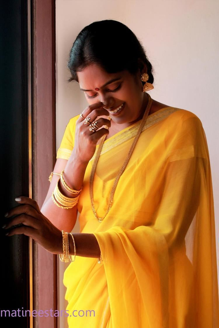 Archana (actress) wearing earrings, a gold necklace, rings, bracelets, and a yellow dress.