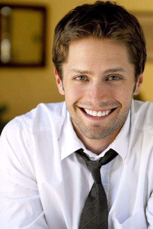 Brett Chukerman smiling while wearing white long sleeves and black necktie