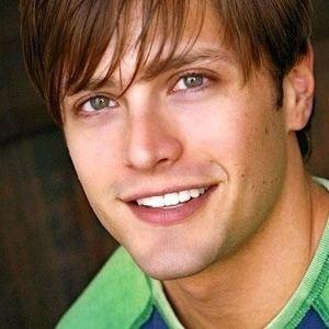 Brett Chukerman smiling while wearing a green and blue t-shirt