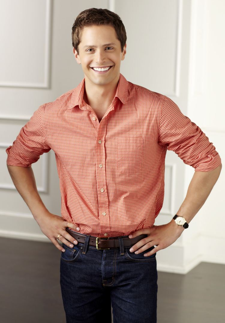 Brett Chukerman smiling while hands on his hips and wearing orange checkered long sleeves