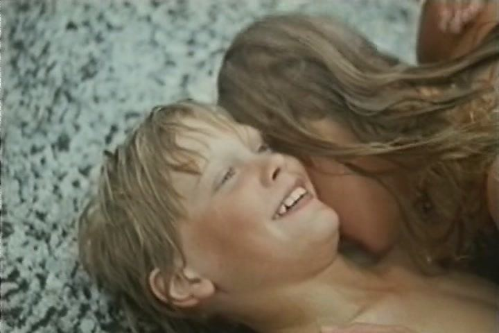 """A scene from """"Children's Island"""" featuring Tomas Fryk as Reine Larsson and a girl lying on the ground."""
