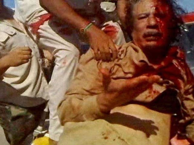 Muammar Gaddafi with blood on his face after the attack.