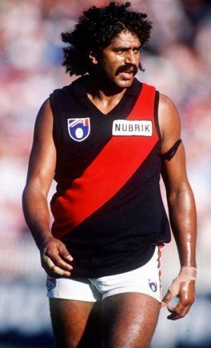 Derek Kickett with curly black hair and a mustache, wearing a red and black jersey and white shorts.