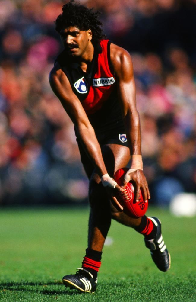 Derek Kickett with curly black hair, wearing a red and black jersey, black shorts, black and white shoes, red and black socks, and holding a football ball.