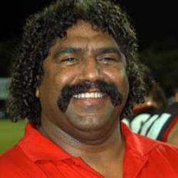 Derek Kickett smiling, with a mustache and curly black hair and wearing a red shirt.