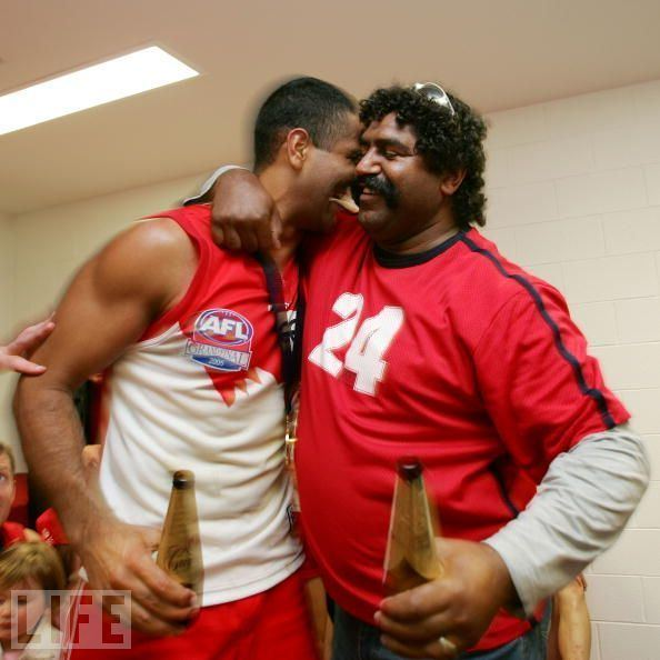 Derek Kickett with a mustache, with curly hair and sunglasses on top of it, wearing a red shirt, holding a bottle of beer while embracing a man wearing a white and red sleeveless shirt and red shorts while holding a bottle of beer.
