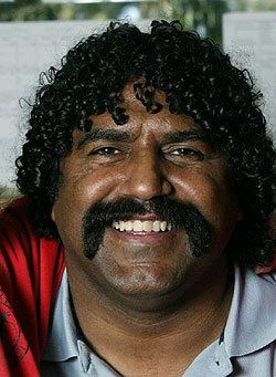 Derek Kickett smiling with a mustache, with curly black hair, wearing a gray polo shirt and red jacket.