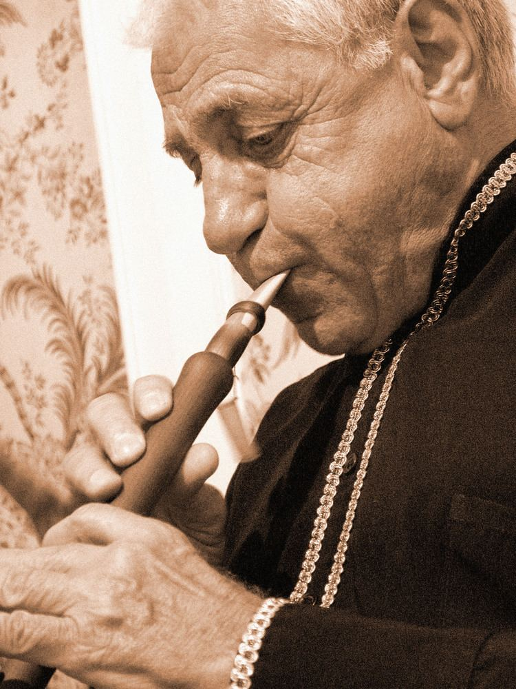 Djivan Gasparyan playing the flute while wearing black and gold long sleeves