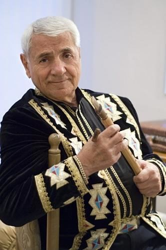 Djivan Gasparyan smiling while holding the flute and wearing a black and gold long sleeves