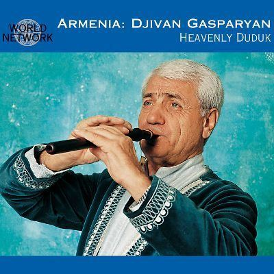 Djivan Gasparyan playing the flute while wearing a white and blue long sleeves