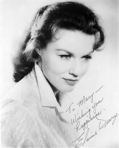 A picture of Elaine Devry wearing a white shirt with her autograph.