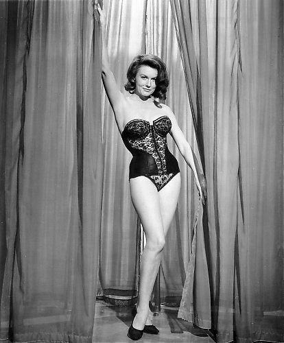 Elaine Devry wearing black sexy lingerie and black shoes while holding the curtains.