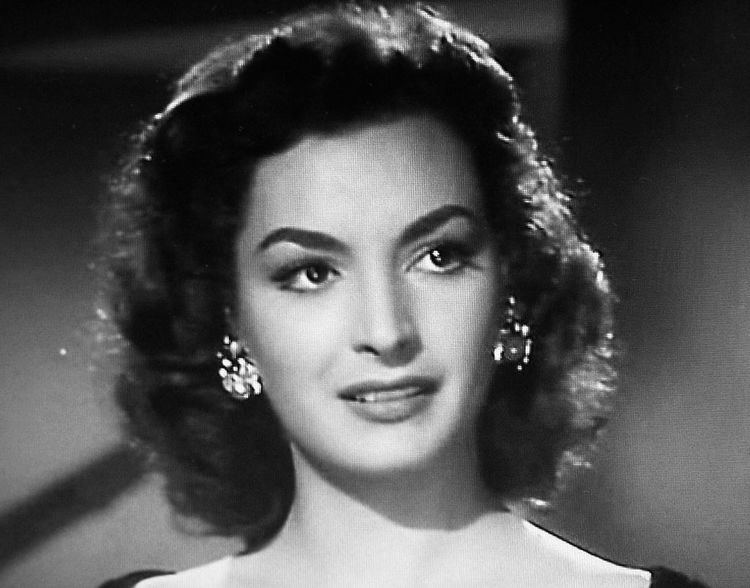 Elsa Aguirre with curly hair and wearing earrings