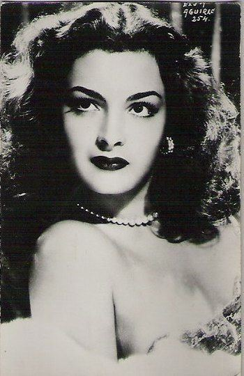 Elsa Aguirre with curly hair while wearing pearl necklace and earrings
