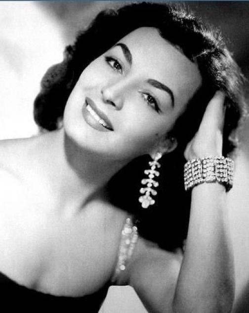 Elsa Aguirre smiling while wearing earrings and bracelet