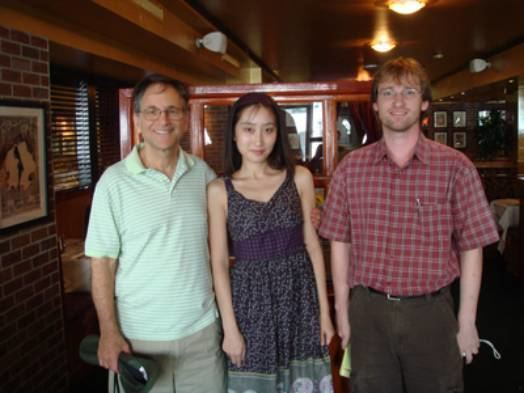 Erik Winfree smiling and wearing a red checkered polo while Lulu Qian wearing a violet dress and the man beside him wearing a polo shirt