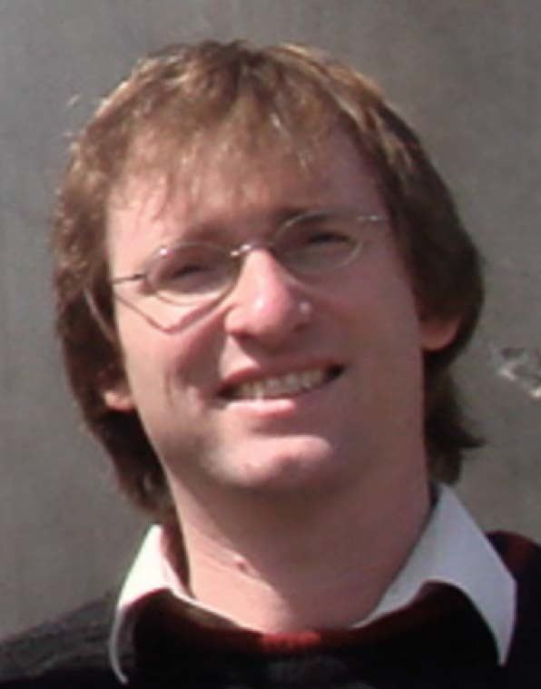 Erik Winfree smiling while wearing eyeglasses and black and white polo