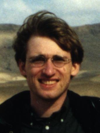 Erik Winfree smiling while wearing black polo and eyeglasses