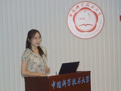 Lulu Qian giving a speech while wearing a floral dress and eyeglasses