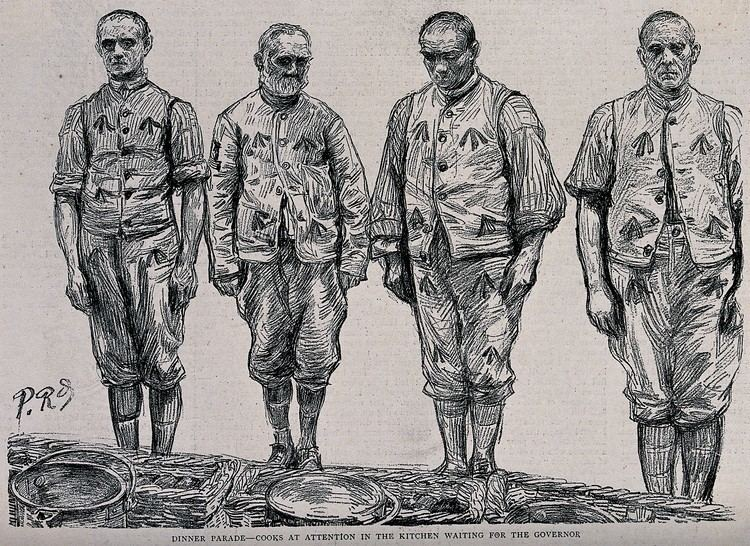 Four Men in Prison FileFour men in prison uniform are standing in a line in front o