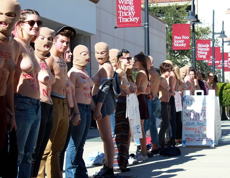 Topless men and women are in the street and some of them are wearing masks
