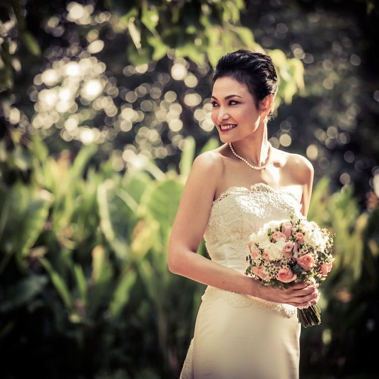 Glenda Chong smiling while holding a bouquet of flowers and wearing white gown and necklace