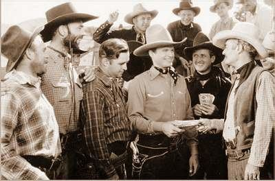 """Bob Baker, Ken Card, Curley Gibson, Herman Hack, Chick Hannan, Art Mix, Lew Morphy, Wally West, and Hank Worden in a movie scene from """"The Singing Outlaw"""" (1937 film)"""