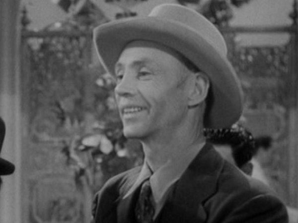 Hank Worden smiling while wearing a hat, coat, long sleeves, and necktie