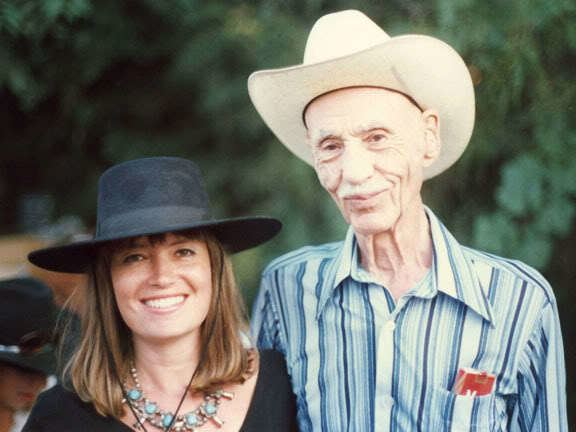 Hank Worden smiling while wearing a hat, and blue striped long sleeves, and the woman beside him smiling & wearing a black hat and black blouse