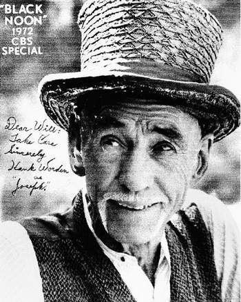 Hank Worden smiling while wearing a hat, vest and long sleeves