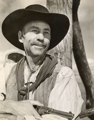 Hank Worden smiling while holding a gun and wearing a hat, long sleeves and vest
