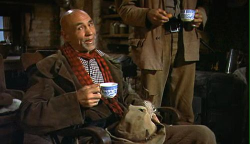Hank Worden smiling while holding a cup and wearing a brown coat, checkered long sleeves, and scarf