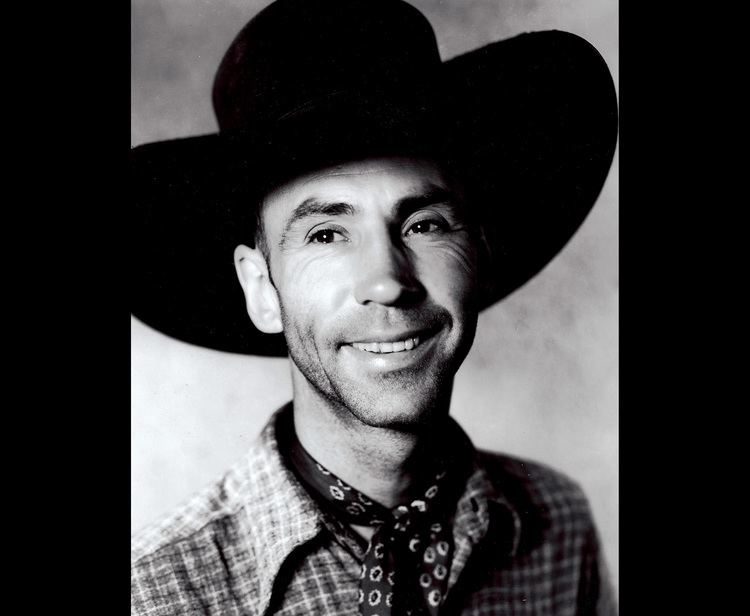 Hank Worden smiling while wearing a hat and checkered long sleeves