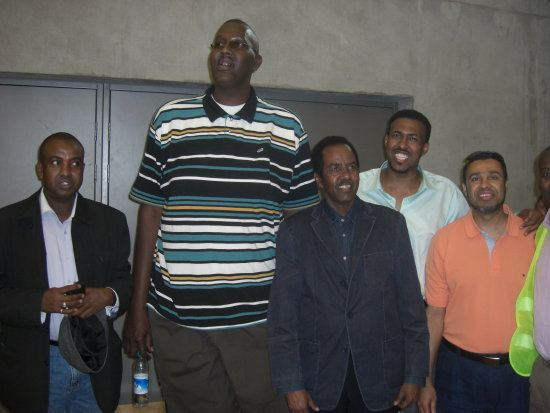 Hussain Bisad looking afar while wearing a striped polo shirt with four men beside him