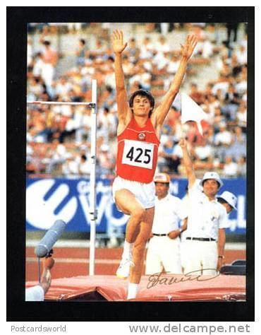Igor Paklin competing in the high jump while wearing a red jersey with the number 425 and white shorts