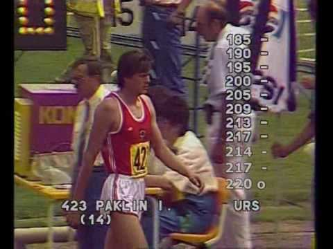 Igor Paklin competing in the high jump while wearing a white and red jersey