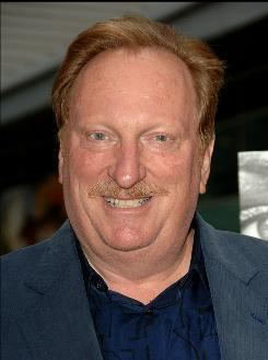 Jeffrey Jones smiling and standing while wearing a formal suit