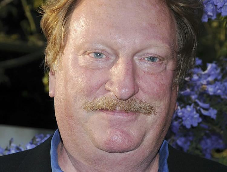 Jeffrey Jones smiles while wearing a black suit with a flower at his back